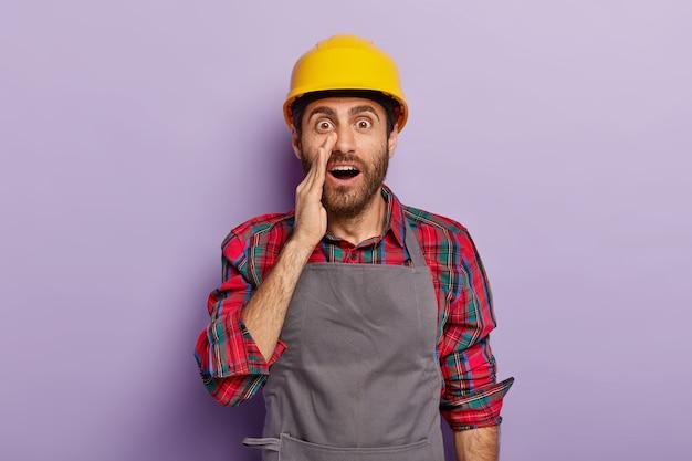 Geheimnisvoll überraschter arbeiter arbeiter schaut mit abgehörten augen