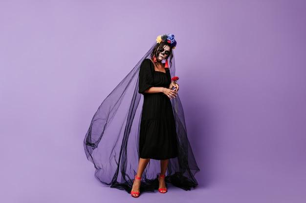 Geheimnisvolle frau hält sanft rote rose. mädchen mit make-up für halloween in schwarzem kleid und schleier.