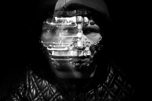Geheimnisvolle mystische erscheinung eines mannes. kunstporträt eines mit kapuze mannes mit großen bergkristallen auf seinem gesicht. große kristalle glitzern im dunkeln auf dem gesicht des mannes. unscharf verschwommen
