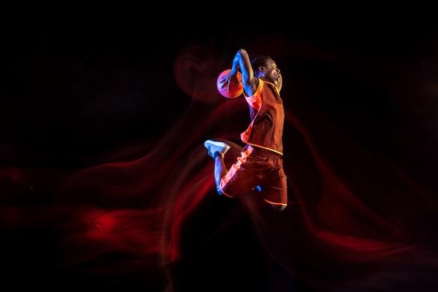Geheimnisvolle natur. afroamerikanischer junger basketballspieler des roten teams in aktion und neonlichtern über dunklem studiohintergrund. konzept von sport, bewegung, energie und dynamischem, gesundem lebensstil.