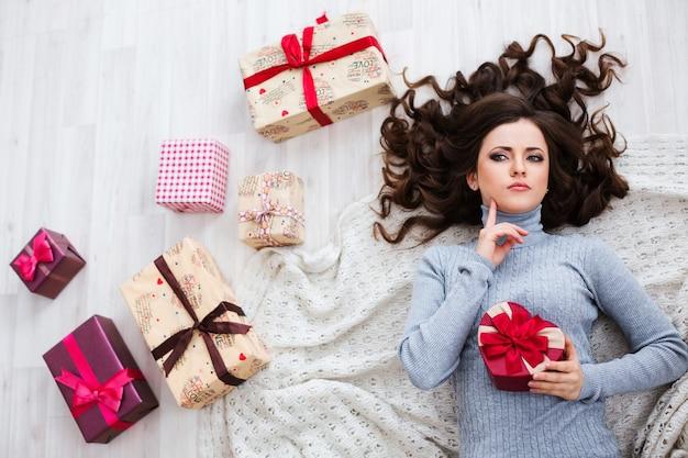 Geheimnisvolle schöne frau, die auf dem boden mit geschenkboxen liegt