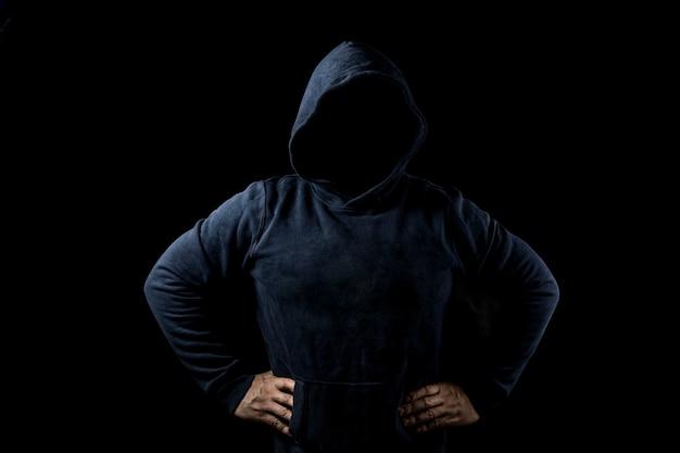 Geheimnisvolle, unbekannte person in der haube. gefahr in der dunkelheit. anonymen oder kriminellen konzept