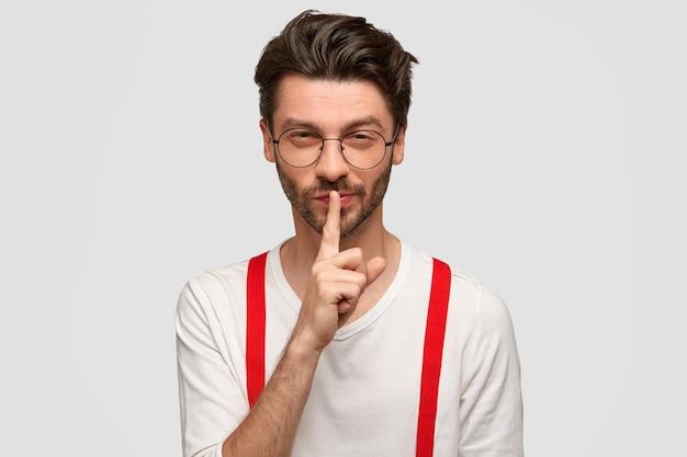 Geheimnisvoller gutaussehender stilvoller kerl mit dunklem haarschnitt, borste, macht leise geste, versucht zu schweigen