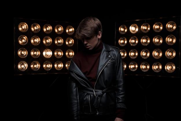 Geheimnisvoller junger mann mit modischer frisur in einer stilvollen lederjacke in burgundergolf und -hose ist im dunkeln drinnen vor dem hintergrund der hellen vintagen scheinwerfer. schöner netter kerl