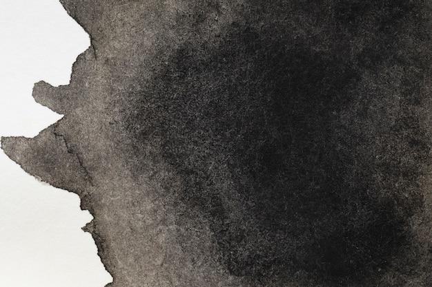 Geheimnisvoller schwarzer handgemalter fleck auf weißer oberfläche