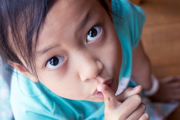 Geheimnisvolles asiatisches kindermädchen des nahaufnahmeporträts, das finger setzt, halten ruhige geste