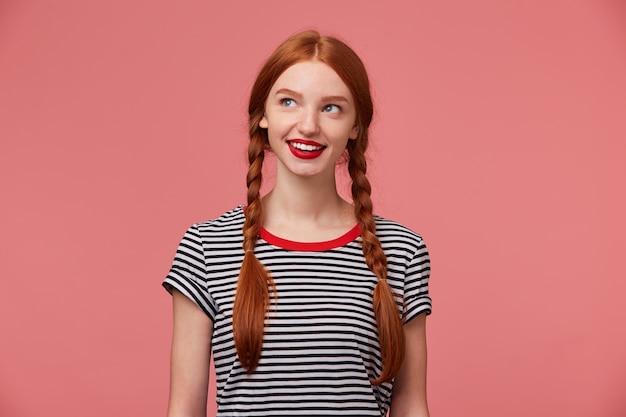 Geheimnisvolles hübsches schönes mädchen mit rothaarigen zöpfen, roten lippen, gekleidet in ein abgestreiftes t-shirt, das mit interesse träumerisch nachdenklich lächelt, schaut in die obere linke ecke, isoliert auf rosa