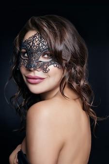 Geheimnisvolles mädchen in einer schwarzen maske, maskerade