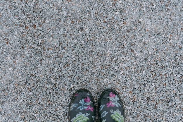 Gehen in gummistiefeln auf grauen kieselsteinen.