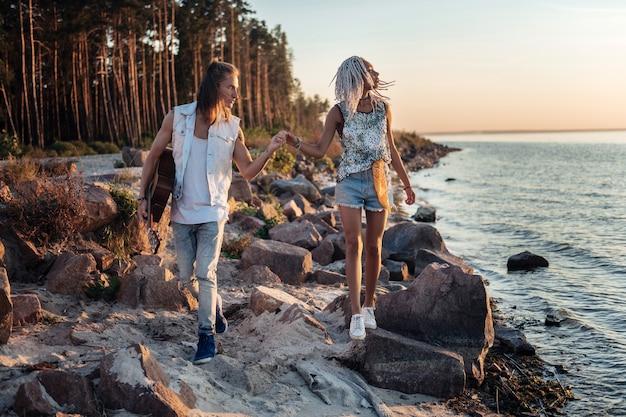 Gehen sie am strand entlang. fürsorglicher blonder mann, der hand seiner freundin hält, während er entlang des felsigen strandes geht