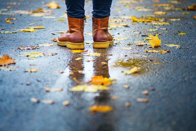 Gehen sie auf einem nassen bürgersteig. hintere ansicht über die füße einer frau, die auf der asphaltpflasterung mit pfützen im regen steht. paar schuhe auf rutschiger straße im herbst. abstrakter leerer freier raum des herbstes weathe