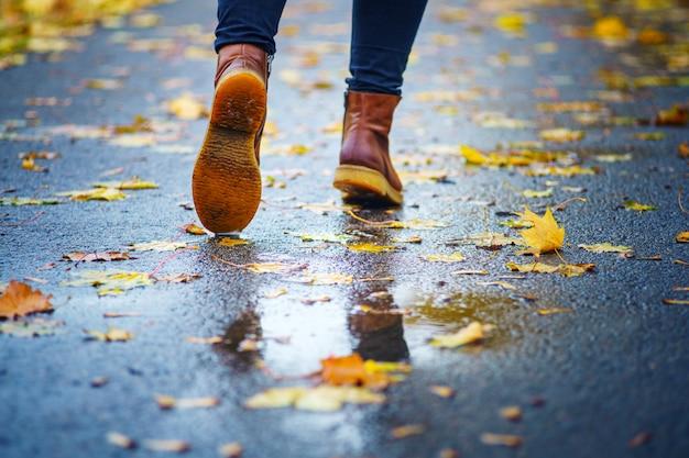 Gehen sie auf einem nassen bürgersteig. hintere ansicht über die füße einer frau, die entlang die asphaltpflasterung mit pfützen im regen geht der fall. abstrakter leerer freier raum des herbstes weathe