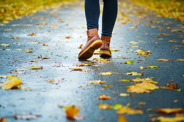 Gehen sie auf einem nassen bürgersteig. hintere ansicht über die füße einer frau, die entlang die asphaltpflasterung mit pfützen im regen geht