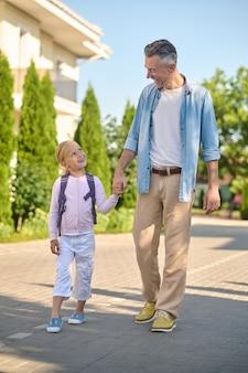 Gehen sie, freier tag. junger erwachsener lächelnder mann, der hand mit kleiner sprechender tochter mit rucksack auf der straße an einem sonnigen tag geht