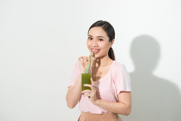 Gehen sie grün. junge schöne frau, die einen gesunden rohen fruchtgemüsesaft genießt.