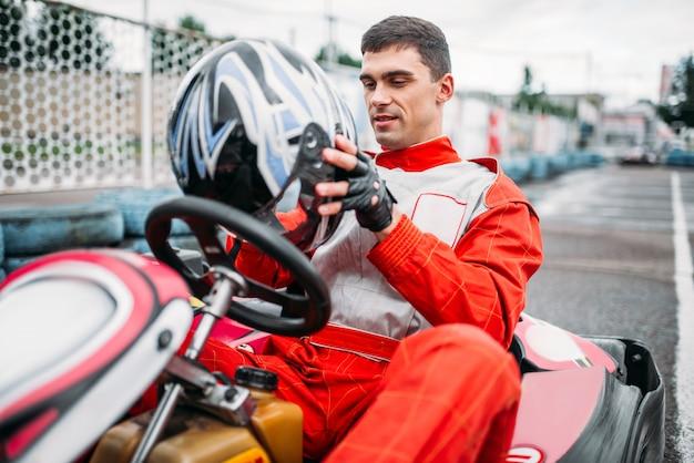 Gehen sie kartfahrer mit helm in den händen auf kart-speed-track. go-kart-motorsport