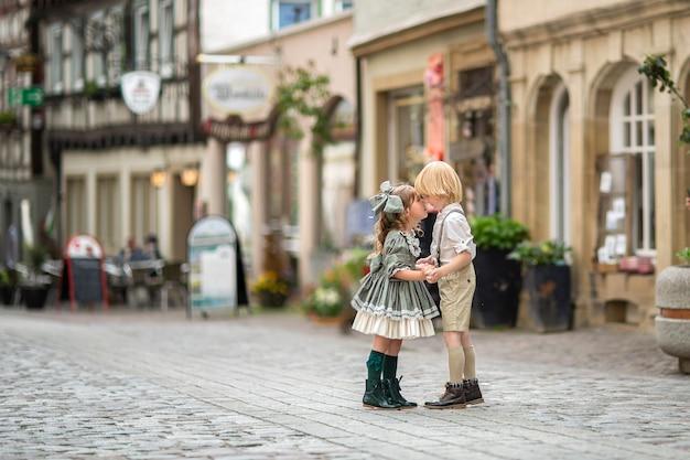 Gehende kinder auf der straße. die beziehung eines mädchens und eines jungen. fotos im retro-stil. fertiger im stadtzentrum. sommer. deutschland