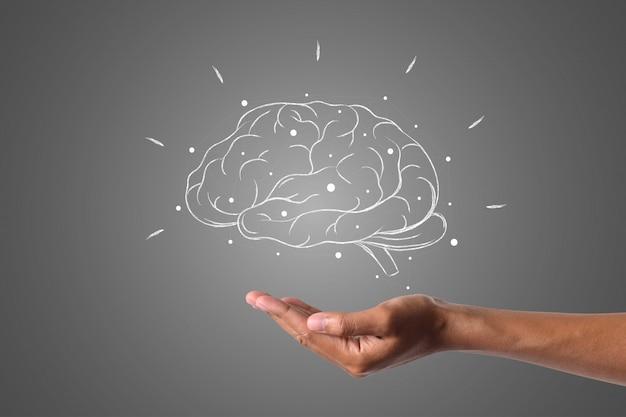 Gehirn schreibt mit weißer kreide ist an hand, konzept zu zeichnen.