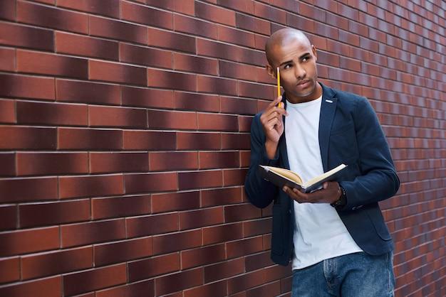 Gehirnentwicklung junger mann, der an der wand steht und ein buch liest, das den kopf mit bleistiftdenken berührt