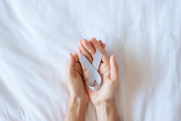 Gehirnkrebs-bewusstseinsmonat, frauenhand, die graues farbband für die unterstützung der lebenden menschen hält. konzept für das gesundheitswesen und den weltkrebstag
