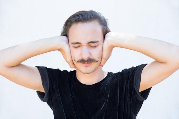 Gehörloser junger mann mit den geschlossenen augen, die ohren bedecken.