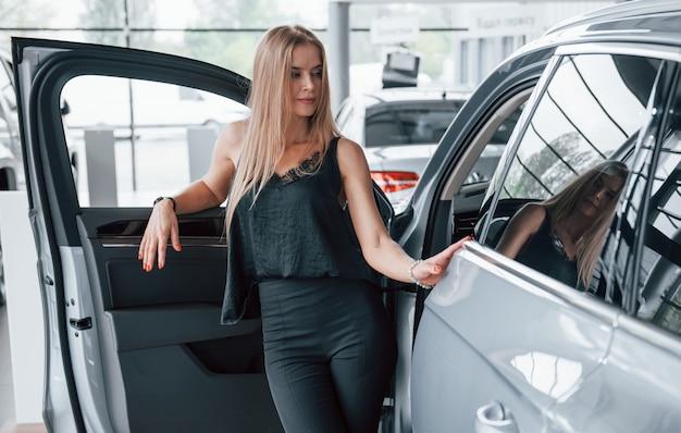 Geht raus. mädchen und modernes auto im salon. tagsüber drinnen. neuwagen kaufen.