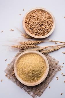 Gehu dalia oder daliya auch bekannt als cracked oder broken wheat, serviert in einer schüssel oder einem löffel