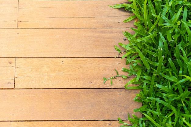 Gehweg aus holzbrettern und grünem gras