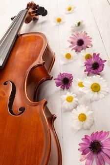Geige mit blumen im weißen hölzernen hintergrund