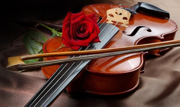 Geige und rote rose auf einem seidentisch in der nähe