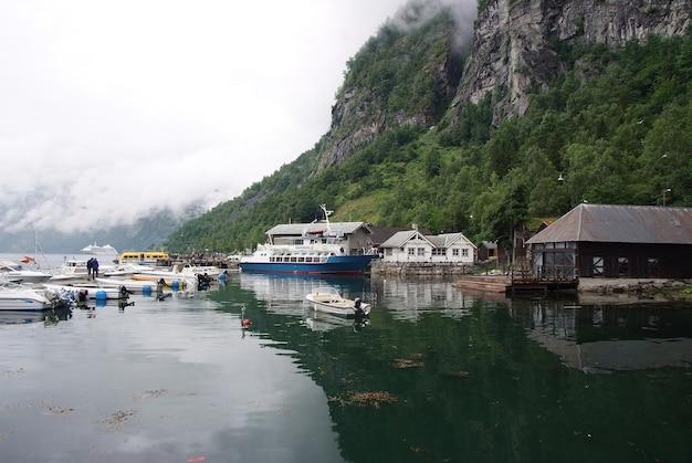 Geiranger, norwegen - 25. januar 2010: dorfhäuser, boote im seehafen auf berglandschaft. wassertransport, schiffe. reiseziel, tourismus. urlaub, reise, fernweh.