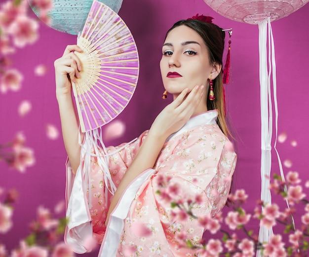 Geisha im rosa kimono und mit einer fächer-nahaufnahme an einer lila wand und mit verschwommenen sakura-blumen