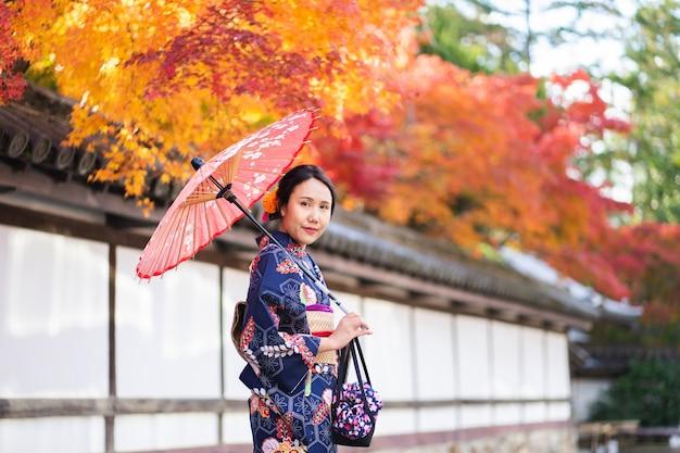 Geishas-mädchen, das japanischen kimono unter rotem hölzernem tori gate trägt
