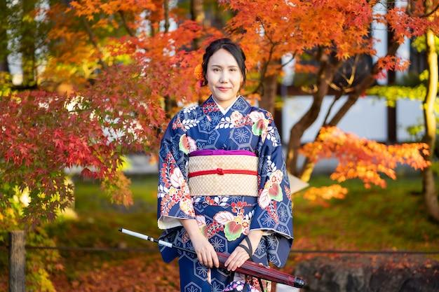 Geishas mädchen, das japanischen kimono unter rotem hölzernen tori-tor am fushimi inari-schrein in kyoto trägt,