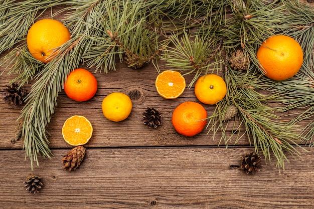 Geist-weihnachten auf holztisch. frische orangen, mandarinen, tannenzweige und zapfen. naturdekorationen, hölzerne bretter der weinlese