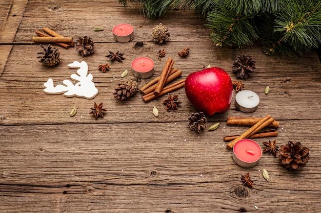 Geist weihnachtsbaum, apfel, kerzen, gewürze, hirsche, zapfen. naturdekorationen, hölzerne bretter der weinlese