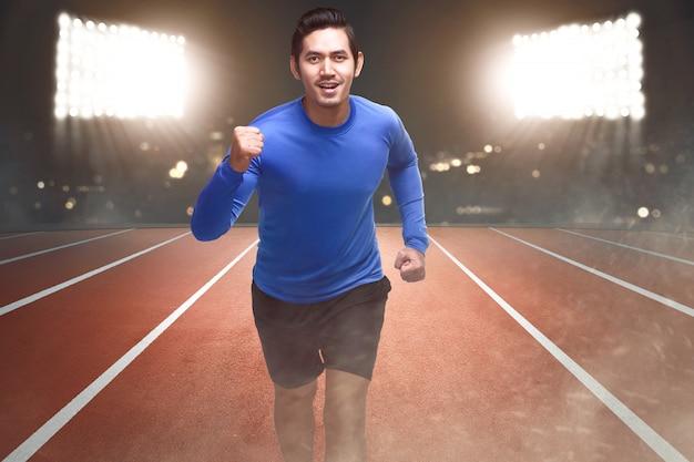 Geistiger asiatischer athlet, der auf der bahn läuft