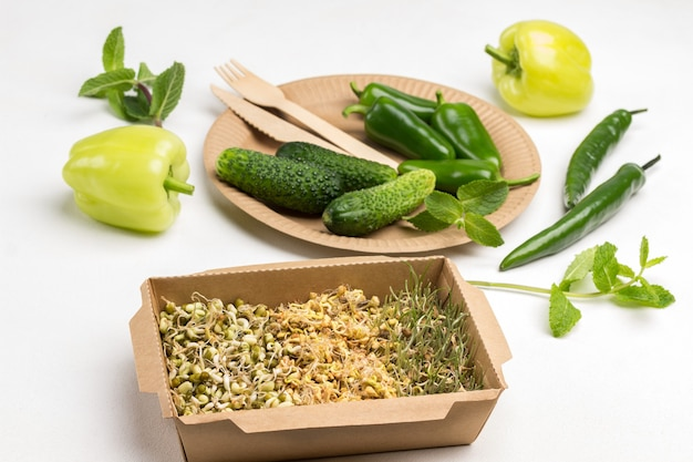 Gekeimte körner von weizen, erbsen und mungobohnen in kartonbehälter. grüner pfeffer in einwegschale aus pappe. minzzweige und gelbe paprika auf dem tisch. weißer hintergrund. ansicht von oben.