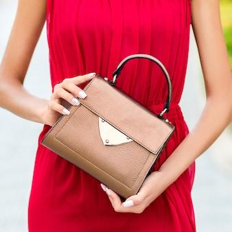 Gekleidet in rote frau, die eine luxushandtasche hält
