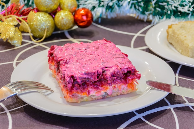 Gekleideter hering oder hering unter einem pelzmantel. symbol des neuen jahres. traditionelle russische küche. weihnachtsschmuck im hintergrund. neujahrskonzept.
