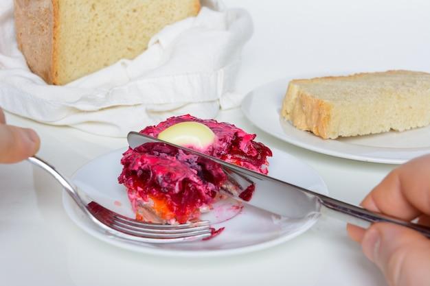 Gekleideter hering oder hering unter einem pelzmantel. traditionelle russische küche. schichtsalat aus gewürfelten eingelegten heringen, bedeckt mit schichten von gekochtem, geriebenem gemüse und mayonnaise.