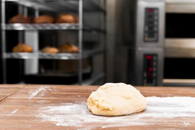 Gekneteter teig mit mehl auf tabelle in der bäckerei