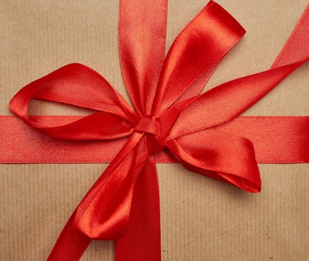 Geknotete schleife aus rotem seidenband auf braunem kraftpapier