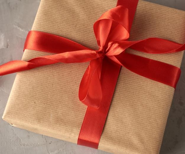 Geknotete schleife aus rotem seidenband auf braunem kraftpapierhintergrund