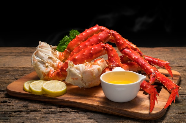 Gekochte bio alaskan king crab beine mit butter und zitronen, alaskan king crab auf holzteller