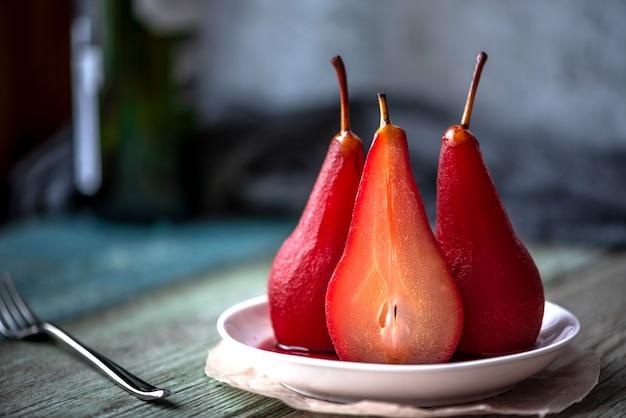 Gekochte birnen in gewürzen und wein. festliches essen. unscharfer hintergrund.