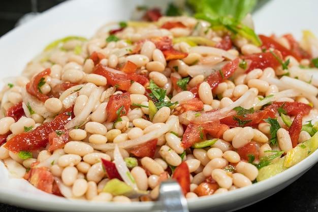Gekochte bohnen mit tomaten, gemüse, zwiebeln und paprika, nahaufnahme. food-konzept