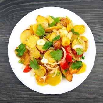 Gekochte bratkartoffeln mit kräutern und gemüse in einem weißen teller auf einem holztisch