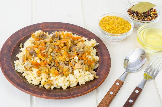 Gekochte bulgurgrütze mit gedünstetem gemüse und pilzen, vegetarisches essen