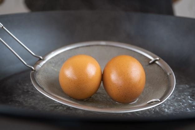 Gekochte eier aus gekochtem wasser nehmen